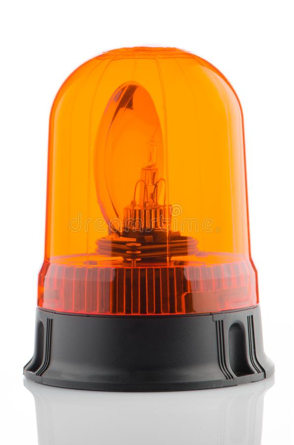 Orange rotating beacon. On white reflective background royalty free stock photo