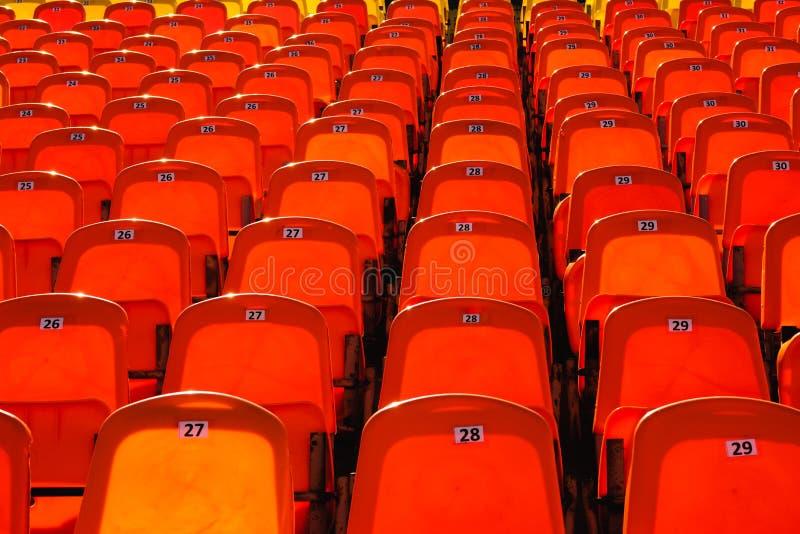 Bright orange rows of seats in the stadium. Orange rows of seats in the stadium. perspective from the ranks stock image