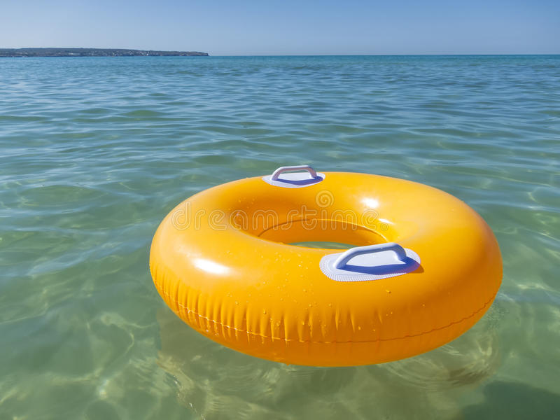 Orange rubber ring in the sea. Orange rubber ring floating empty in the sea royalty free stock photography