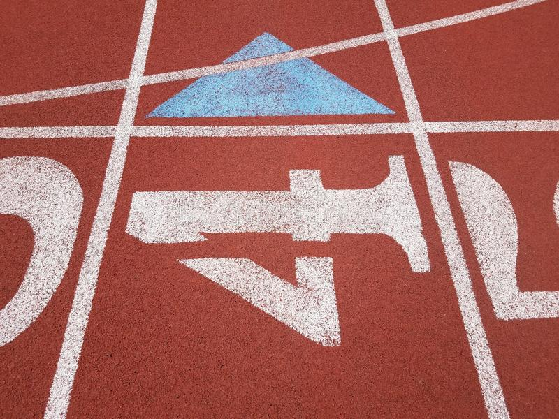 Orange running track with the number 4 and a blue triangle stock images