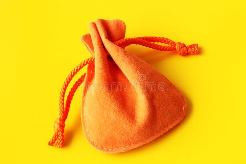 Orange säck för gåvor på gul bakgrund royaltyfri bild