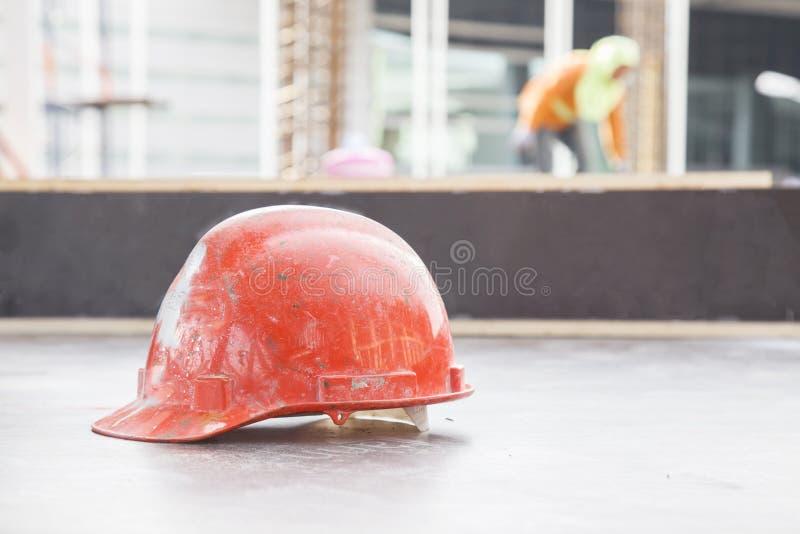 Orange säkerhetshjälm i konstruktion med arbetarbakgrund arkivfoto