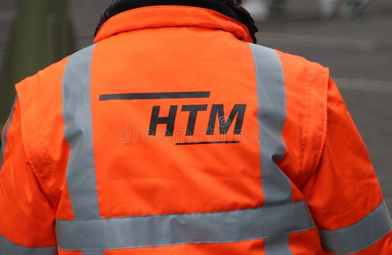 Orange safety jacket of engineer of HTM, responsible for local public transportation in the hague. Orange safety jacket of engineer of HTM, responsible for stock images