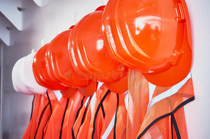 Orange safety vests and orange safety helmets. On the hooks on the wall in an industrial placement royalty free stock image