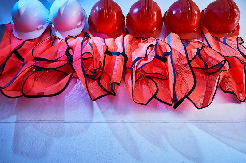 Orange safety vests and orange safety helmets. On the hooks on the wall in an industrial placement stock image
