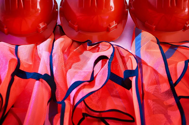 Orange safety vests and orange safety helmets. On the hooks on the wall in an industrial placement royalty free stock photos