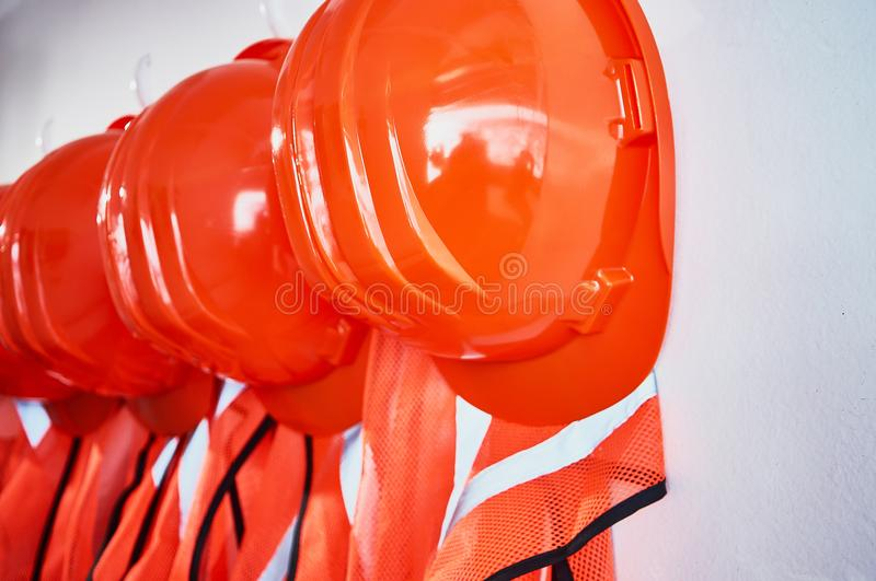 Orange safety vests and orange safety helmets. On the hooks on the wall in an industrial placement stock photos