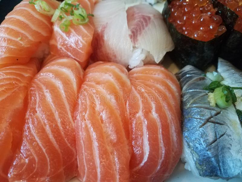 Orange salmon sushi and salmon eggs with chives stock photography
