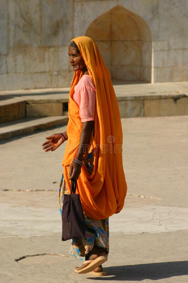 In an orange sari. An Indian lady walks across the fort at Amber Fort in Jaipur, the sun lightens up her orange sari