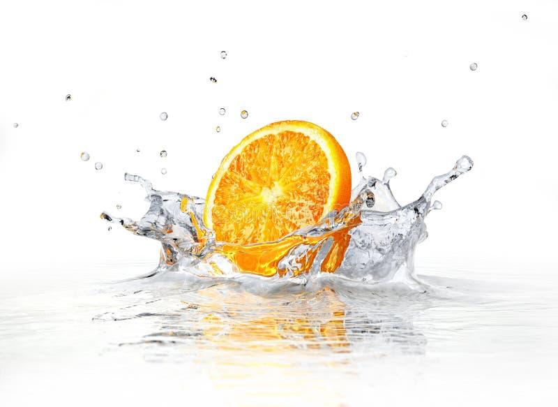 Orange Scheibe, die in klares Wasser fällt und spritzt. lizenzfreie stockbilder