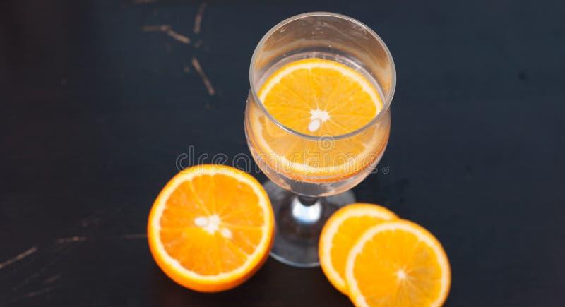 Orange Scheibe im Glas, die Ansicht von der Spitze, auf einem schwarzen hölzernen Hintergrund, Nahaufnahme, stockfotos