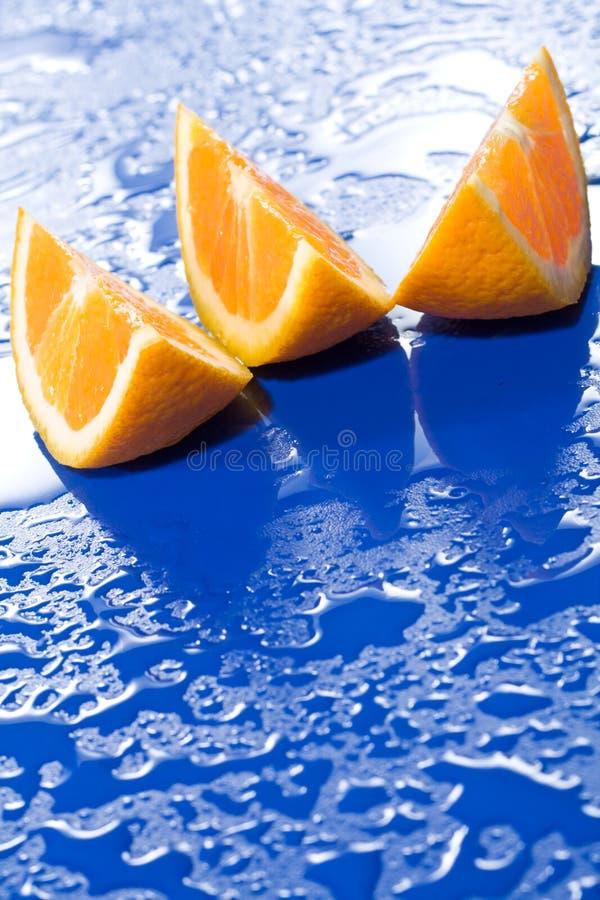 Orange Scheiben auf blauer Oberfläche lizenzfreie stockfotos
