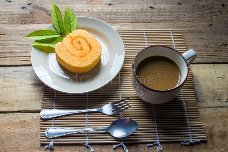 Orange Scheibenrollenkuchen und -kaffee lizenzfreie stockfotografie
