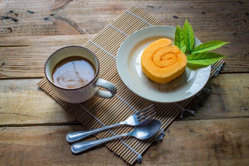 Orange Scheibenrollenkuchen und -kaffee lizenzfreie stockfotos