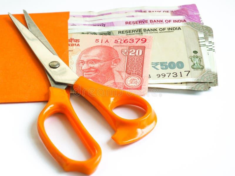 Orange Scheren auf das indische Geld im orange Umschlag stockfotos