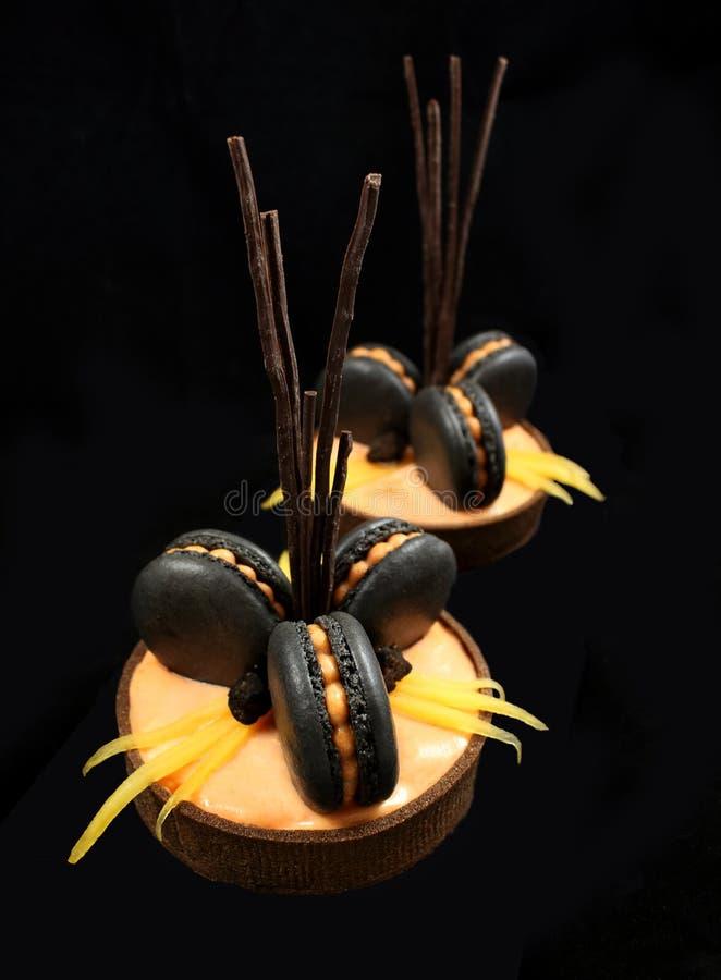 Orange Schokoladentörtchen mit schwarzen französischen macarons und Persimone auf schwarzem Hintergrund lizenzfreies stockfoto