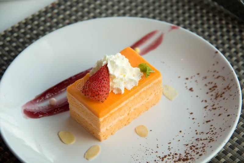 Orange Schwamm-Kuchen auf einer weißen Platte lizenzfreies stockfoto