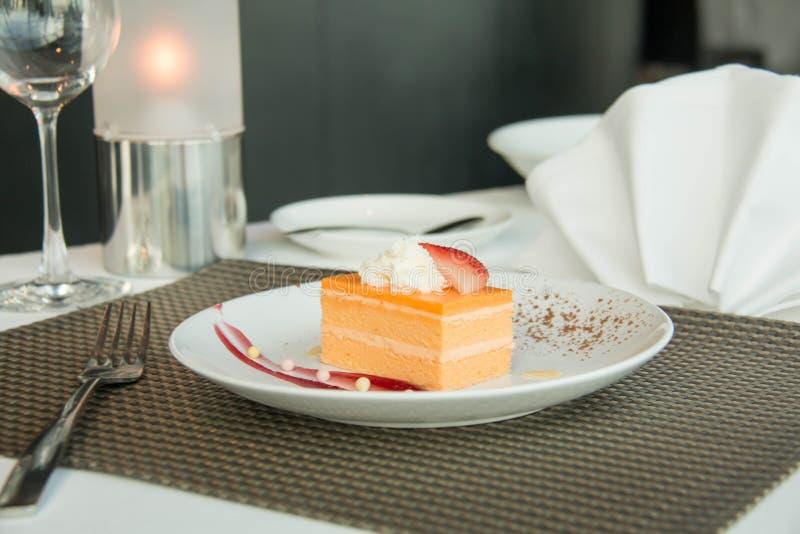 Orange Schwamm-Kuchen auf einer weißen Platte stockfotografie
