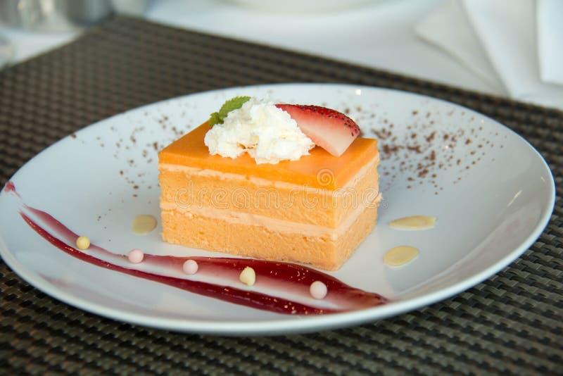 Orange Schwamm-Kuchen auf einer weißen Platte lizenzfreies stockbild