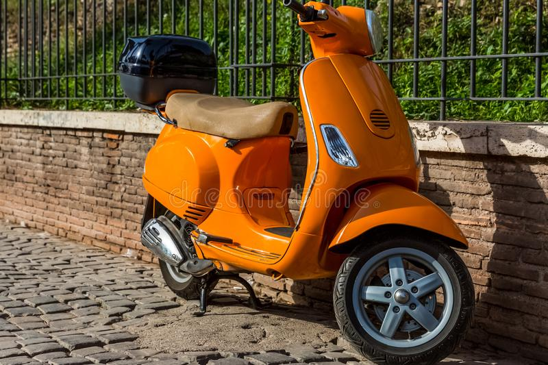 Orange scooter parked near the fence on the stock photos