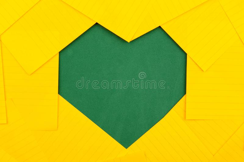 Orange sheets of paper lie on a green school board and form a frame heart shape stock images