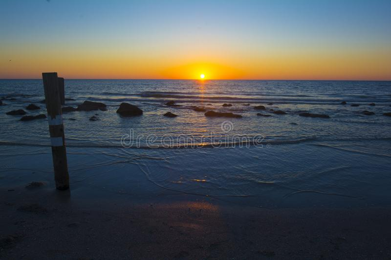 Ocean beach dramatic sunsets calm water. Orange skies and blue waters of the florida Gulf of Mexico as the sunsets. calm water sun on horizon line royalty free stock photos