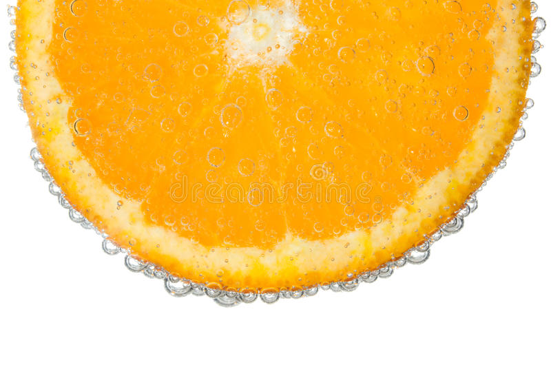 Orange skiva i klar mousserande vattenbubblabakgrund royaltyfria foton