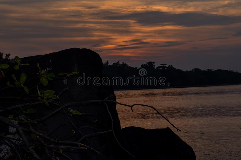 Orange sky above it with awesome sun golden reflection on calm waves as a background. Amazing summer sunset view on the beach royalty free stock photo