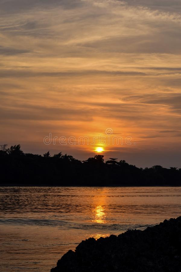 Orange sky above it with awesome sun golden reflection on calm waves as a background. Amazing summer sunset view on the beach.  royalty free stock photography