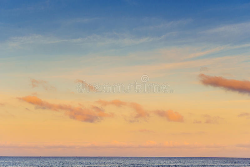 Orange sky, above the blue sea. Small clouds royalty free stock photo