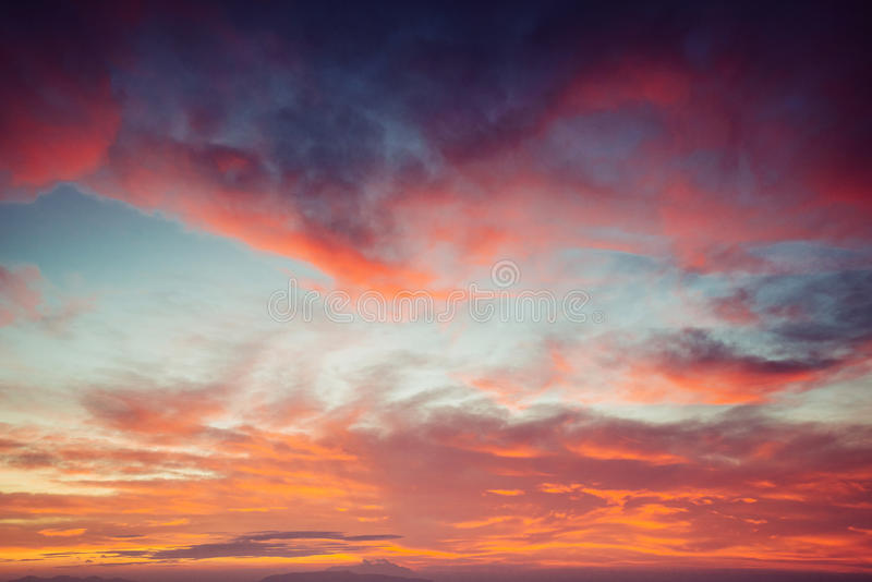 Orange sky, above the blue sea. Small clouds royalty free stock images