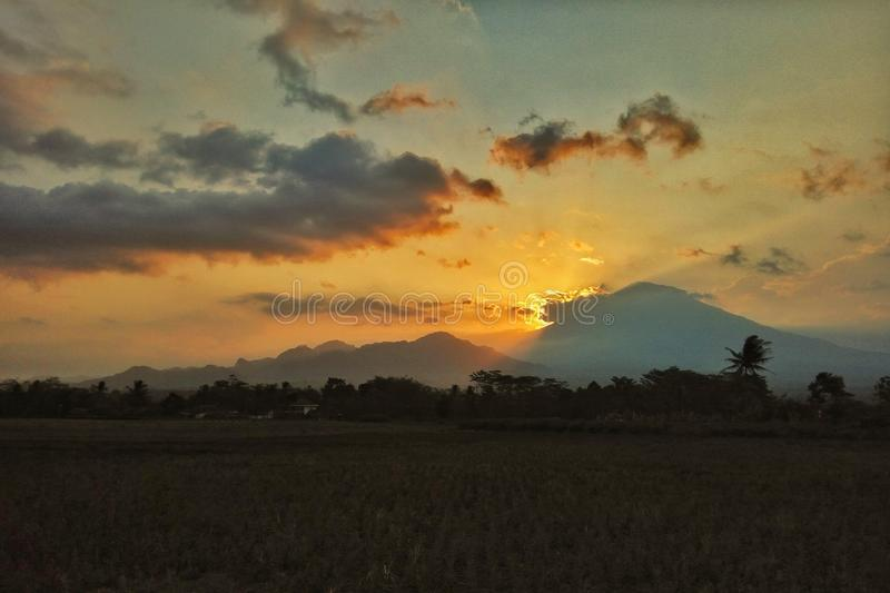 THE ORANGE SKY. THE LIGHT OF SUN FADING AWAY TROUGH THE MOUNTAIN stock images