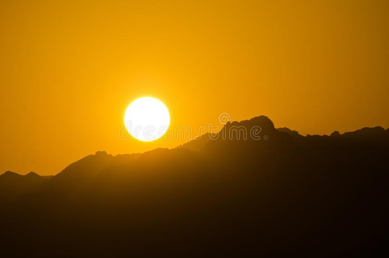 Orange sky of sun during sunset above mountains in Sinai desert, Egypt.  royalty free stock photos