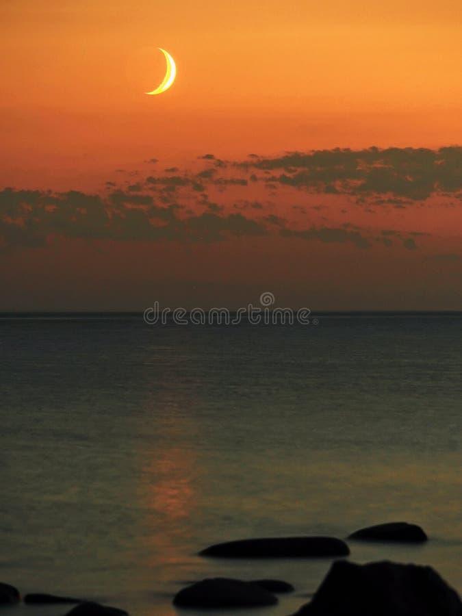 Moon set and orange sky over sea stone coast stock image
