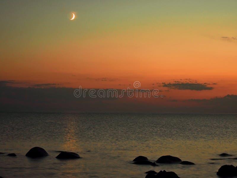 Moon set and orange sky over sea stone coast royalty free stock photo