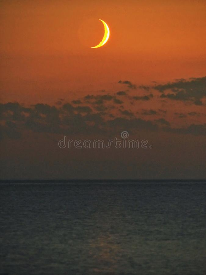 Moon set and orange sky after sunset stock photography