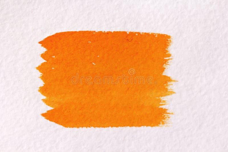 Orange slaglängd med en borste som göras av vattenfärger tätt papper för bakgrund som skjutas upp royaltyfria foton