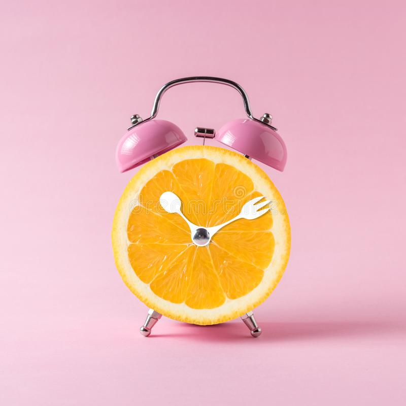 Orange slice alarm clock on pink background. Minimal business concept.  stock images