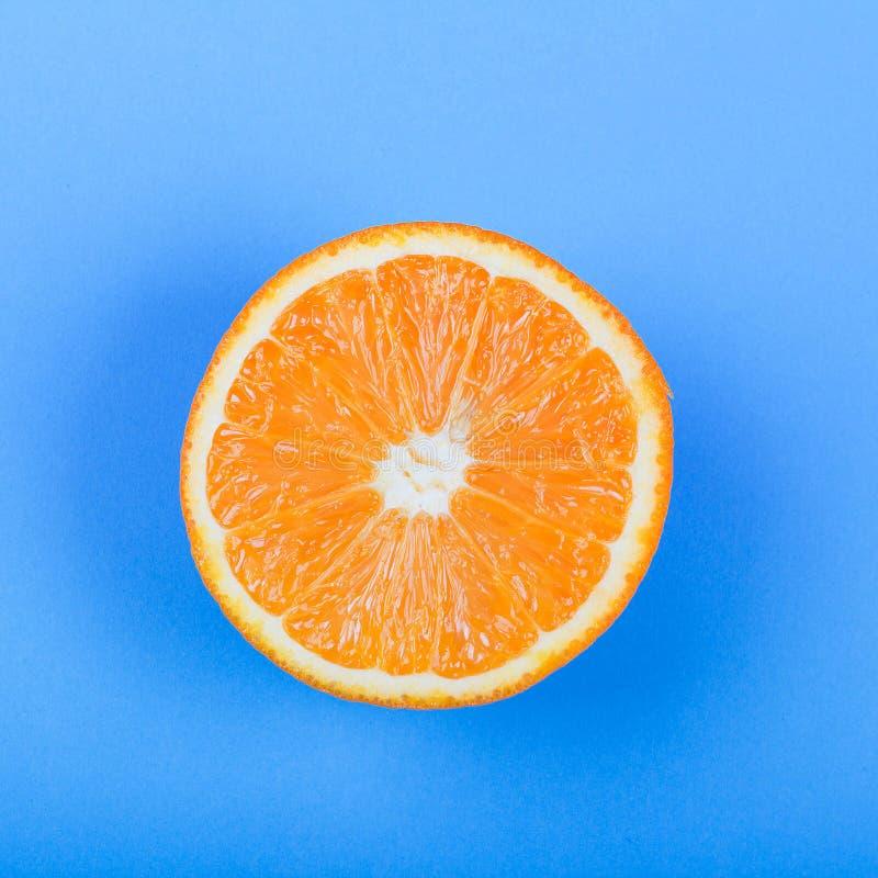Orange slice on blue background. Fresh orange slice on blue background citron citrus clipping path closeup color cut cutout dessert diet eating exotic food fruit royalty free stock photo
