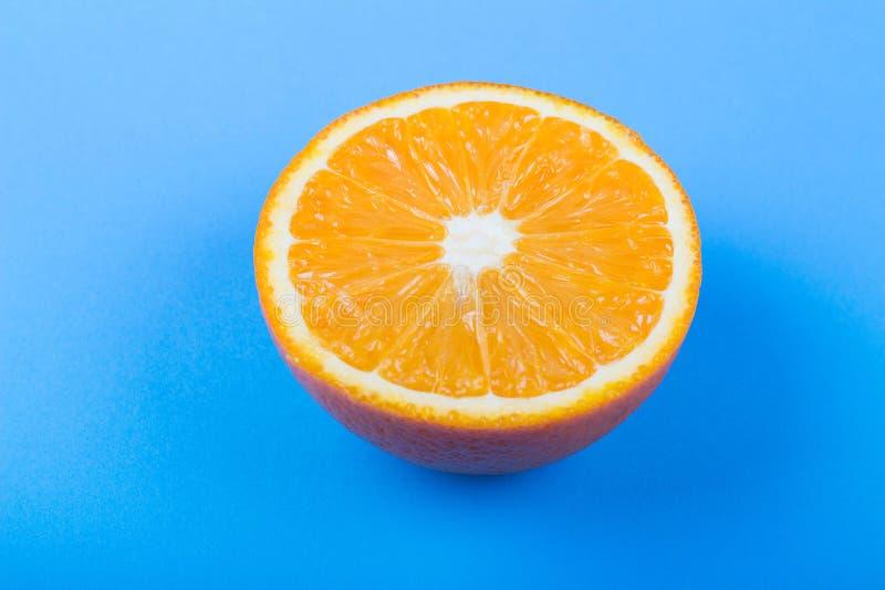 Orange slice on blue background. Fresh orange slice on blue background citron citrus clipping path closeup color cut cutout dessert diet eating exotic food fruit stock photos