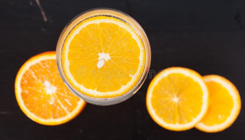 Orange slice in the glass, the view from the top, on a black wooden background, closeup, royalty free stock photo