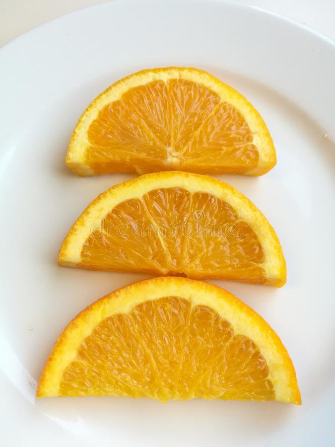 Orange slice isolated on white plate, 3 pieces of fresh sliced orange fruit with skin collection royalty free stock photo