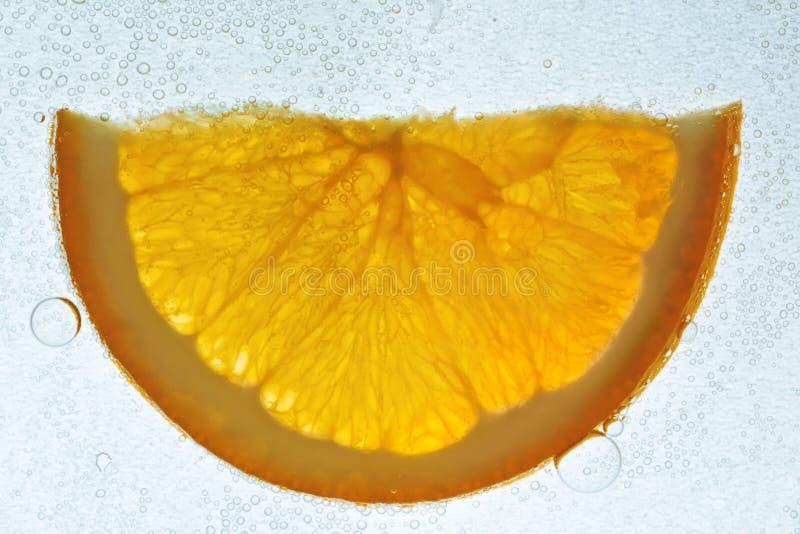 Orange slice in soda water. Transparent orange slice in soda water, closeup, white background stock images