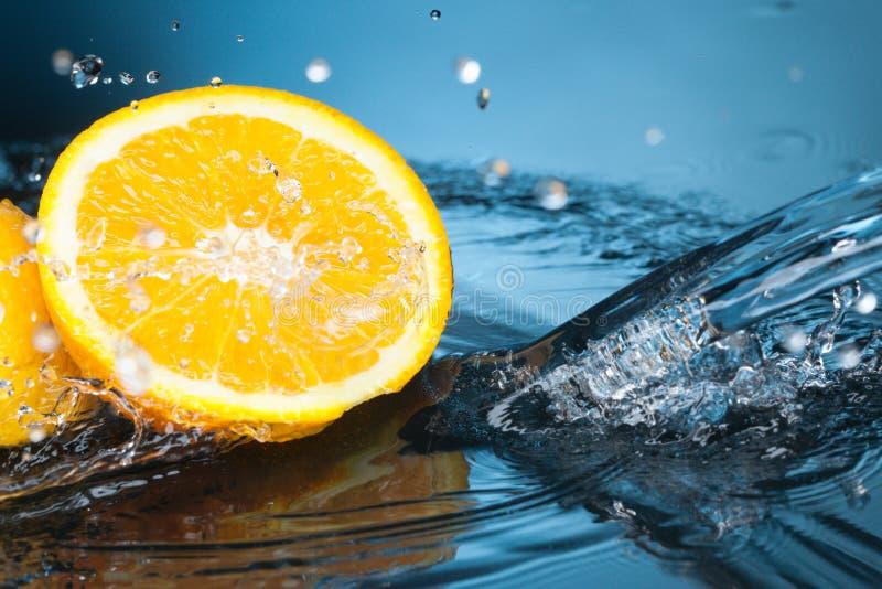 Orange slice in water stream royalty free stock photos