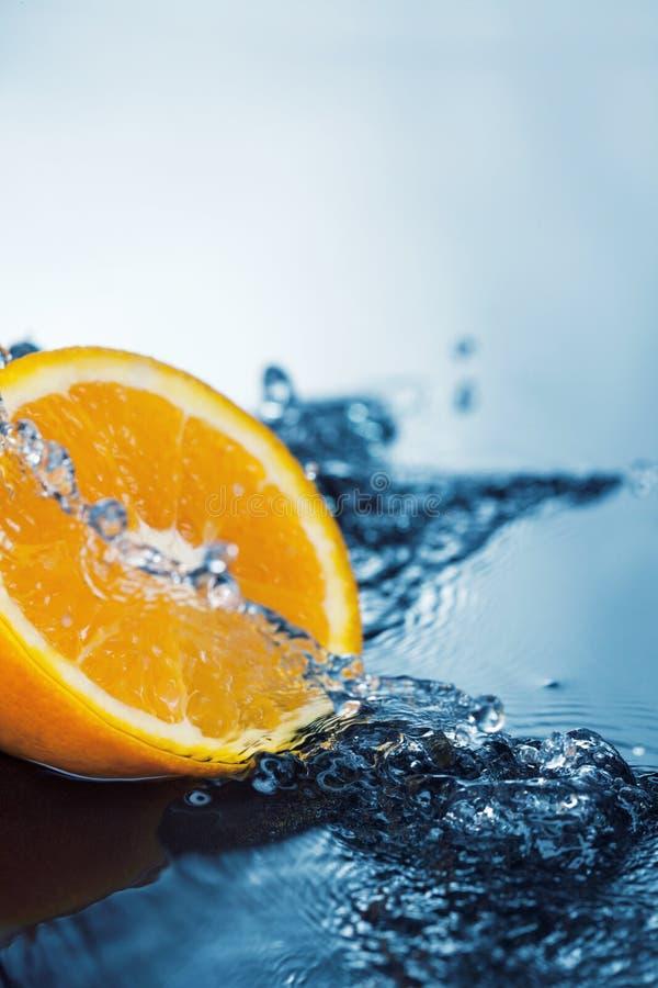 Orange slice in water stream stock images