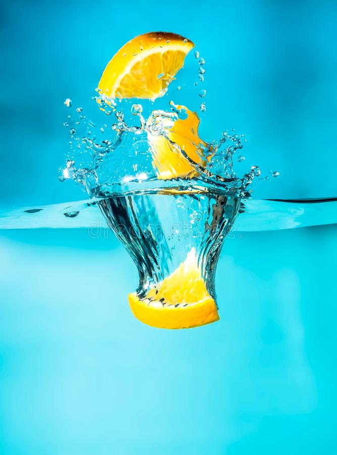Orange slices falling into the blue water close-up, macro, splash water, bubbles. Bright photo. royalty free stock images
