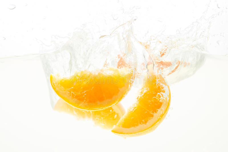 Orange Slices falling deeply under water with a big splash royalty free stock image