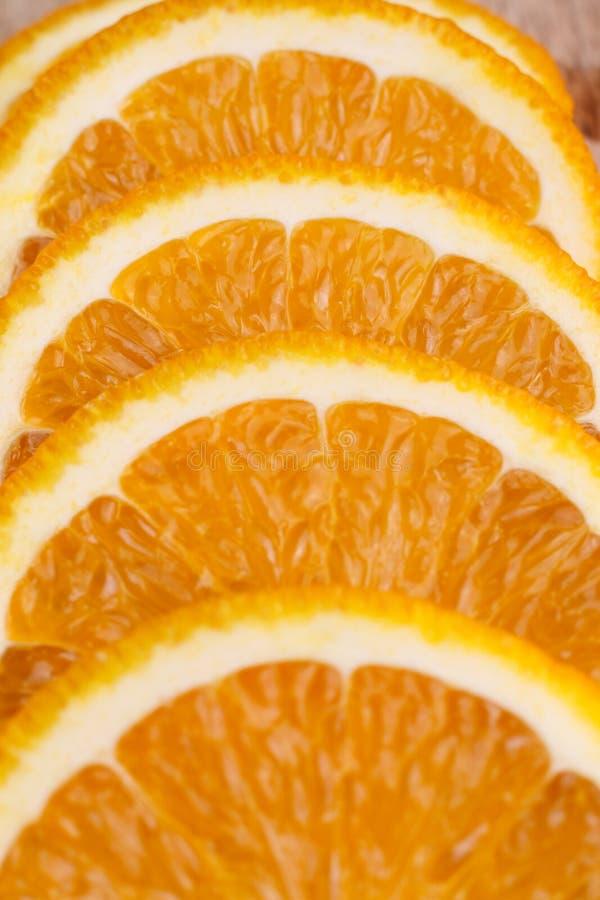 Orange slices lie on a kitchen wooden board. Close-up stock image