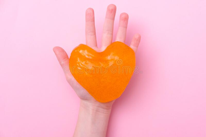 Orange slime in heart shape in kid hands. Girl hands playing slime toy on pink background. Making slime. Love and stock image