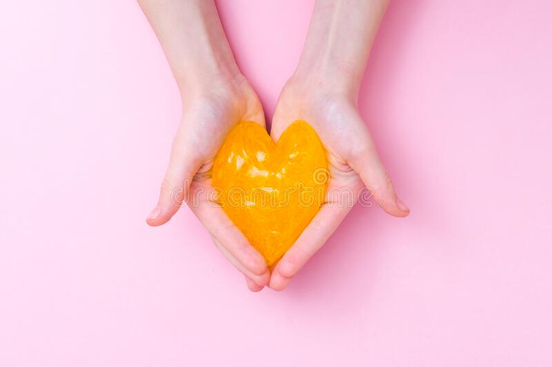 Orange slime in heart shape in kid hands. Girl hands playing slime toy on pink background. Making slime. Love and stock photography